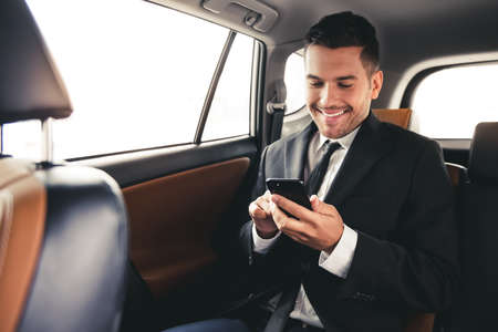 Handsome businessman in suit is using a smart phone and smiling while sitting on back seat in the car Archivio Fotografico