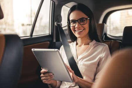 眼鏡で美しいビジネス女性はデジタル タブレットを使用して、車の後部座席に座って笑顔
