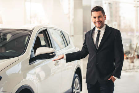Handsome businessman in suit is looking at camera and smiling while standing near the car in car dealership