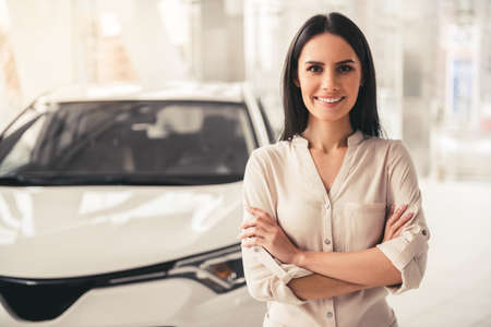 Visiting car dealership. Beautiful young woman is looking at camera and smiling while standing with crossed arms near her new car