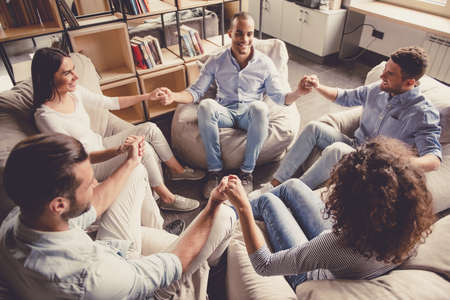 Young people are sitting in circle, holding hands and smiling Stock Photo - 75076813
