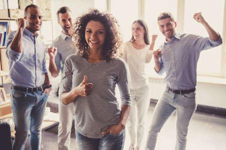 成功したビジネス人々 は手拳で事務所に立っている間幸せで悲鳴を上げています。一人の女の子の Ok サインを見せています。 写真素材