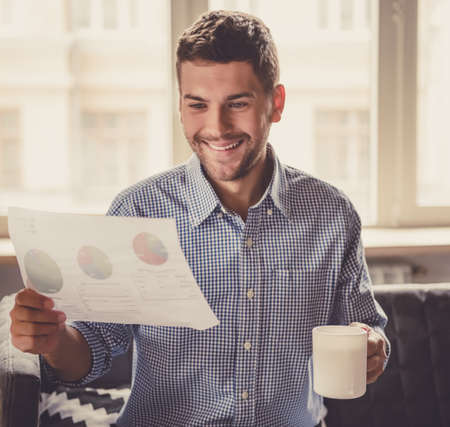 Handsome businessman is drinking coffee, studying document and smiling while working in office Stock Photo