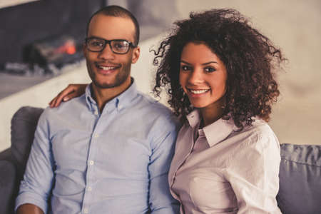 couple on couch: Beautiful young Afro American couple is looking at camera and smiling while sitting on couch at home
