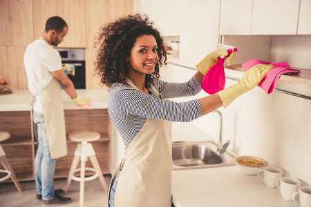 kitchen furniture: Beautiful young Afro American couple is cleaning kitchen. Girl is looking at camera and smiling Stock Photo
