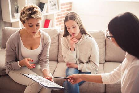 ママと 10 代の娘は、理学療法士を訪れています。医師は患者を聞いて、ノートを作る