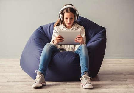 Onrustige tienermeisje zit op zit-stoel en het gebruik van een digitale tablet