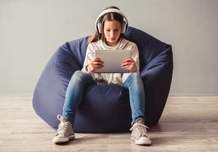 Troubled teenage girl is sitting on bean-bag chair and using a digital tablet