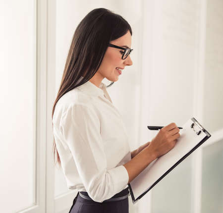 business help: Beautiful young psychotherapist is making notes and smiling while standing in office