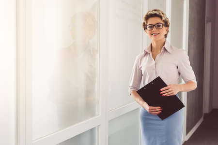 Beautiful psychotherapist in suit and eyeglasses is holding a folder, looking at camera and smiling while standing in office