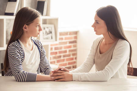 Troubled teenage girl and her mom are looking at each other and talking while sitting at home Foto de archivo