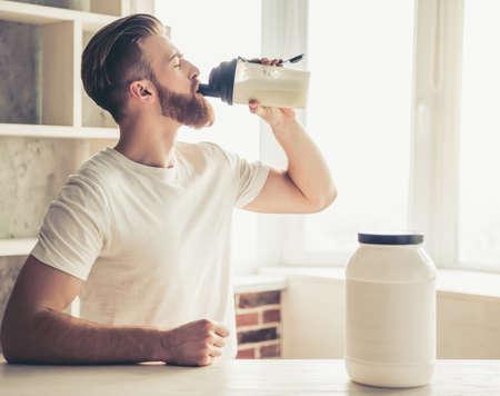 自宅の台所でスポーツ栄養の準備中にハンサムな若いひげを生やしたスポーツマンを飲む 写真素材