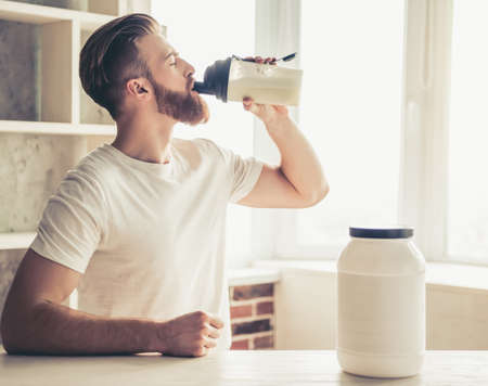 Handsome young bearded sportsman is drinking while preparing sport nutrition in kitchen at home