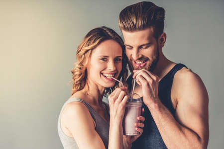Beautiful young sports is drinking nutritious cocktail and smiling, on gray background