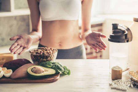 Cropped image of beautiful young sportswoman lifting hands in dismay while choosing between sport supplements and healthy food Stock Photo