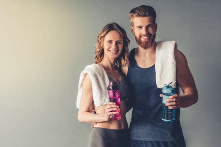Beautiful young sports people are holding bottles of water, looking at camera and smiling, on gray background