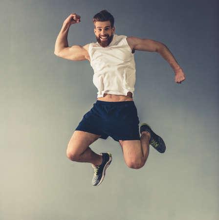 De knappe jonge gebaarde sportman toont spieren, springend en glimlachend, op grijze achtergrond