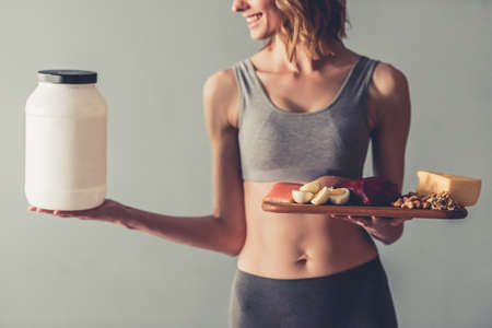 Cropped image of beautiful young sportswoman holding a bottle with sport nutrition and a wooden tray with healthy food, on gray background