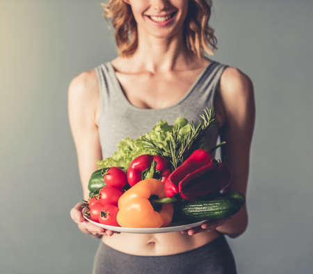 Beautiful young sportswoman is holding a plate with vegetables, looking at camera and smiling, on gray background
