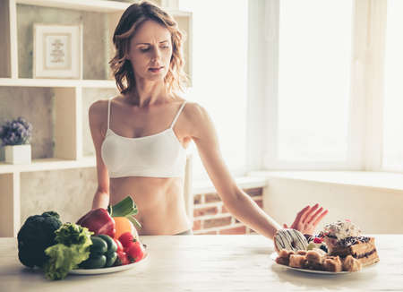 Beautiful young sportswoman is choosing between the plate of vegetables and the plate of cakes in kitchen at home