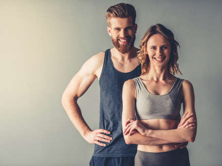Beautiful young sports couple is looking at camera and smiling, on gray background