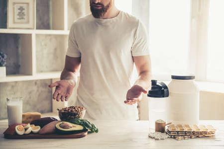 自宅の台所でスポーツ栄養の準備ハンサムな若いスポーツマンのイメージをトリミング 写真素材