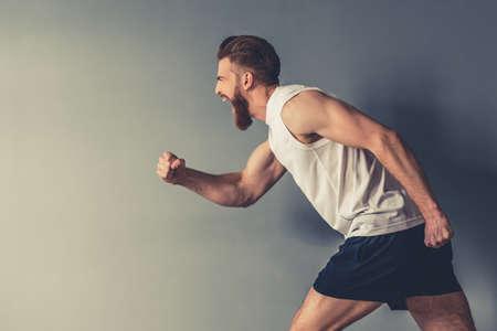 Zijaanzicht van knappe jonge bebaarde sportman die, op grijze achtergrond loopt gilt