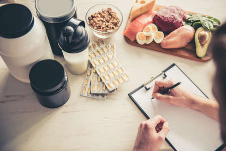Cropped image of handsome young sportsman making notes while preparing sport nutrition in kitchen at home