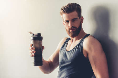 Handsome young bearded sportsman is holding bottle of water and looking at camera, on gray background