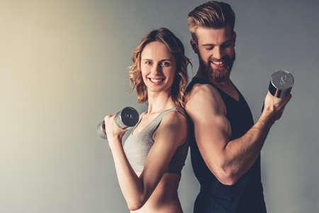 美しい若いスポーツ選手がダンベルでワークアウトや灰色の背景に、笑みを浮かべて 写真素材 - 79149180