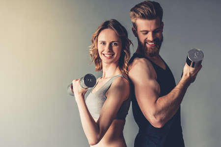 Beautiful young sports people are working out with dumbbells and smiling, on gray background