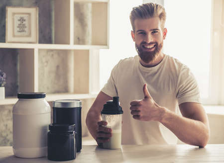 Handsome young bearded sportsman is looking at camera and smiling while preparing sport nutrition in kitchen at home Stock Photo