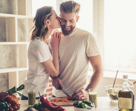 美しい若いカップルが話しているし、自宅の台所で健康食品を調理しながら笑みを浮かべてします。女の子は彼氏に頬にキスします。
