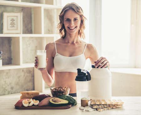 美しい若いスポーツ選手はカメラを見て、自宅の台所でスポーツ栄養の準備中に笑みを浮かべて
