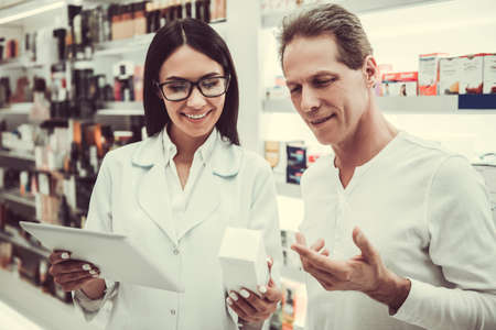 Beautiful young female pharmacist is suggesting a medication to a client at the pharmacy, holding a digital tablet and smiling Stock Photo