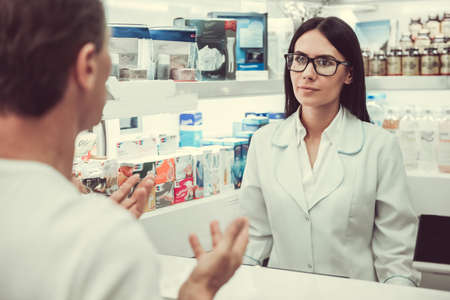 At the pharmacy. Beautiful young female pharmacist is listening to a client while working at the cash desk