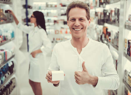 At the pharmacy. Handsome client is holding a medication, showing Ok sign and smiling, beautiful female pharmacist in the background