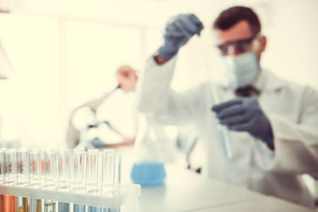 At the laboratory. Test tubes with substances in the foreground, medical doctors are working in the background Stock Photo