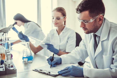 Hermosos médicos en guantes y gafas están trabajando con sustancias en tubos de ensayo y microscopio en el laboratorio Foto de archivo - 76259629