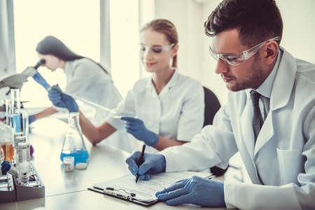 Mooie medische artsen in handschoenen en glazen werken met substanties in reageerbuizen en microscoop in het laboratorium Stockfoto
