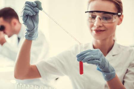 Mooie artsen werken met reageerbuizen en microscoop op het lab