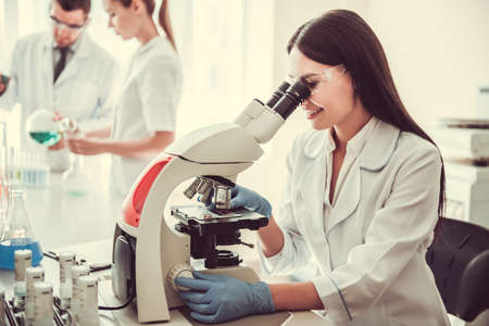 Beautiful medical doctor is using a microscope and smiling while working at the lab