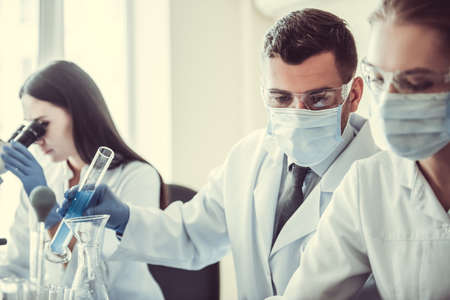 Beautiful medical doctors in gloves, masks and glasses are working with substances in test tubes and microscope at the lab