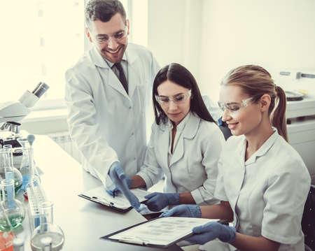 Mooie artsen in handschoenen en een bril bespreken testresultaten tijdens het werken in het lab