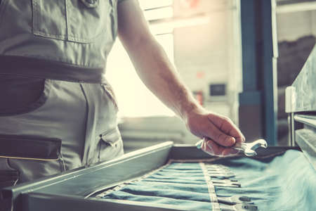オート サービスで車を修理するためのツールを選択する制服でハンサムな若い自動車整備士の画像をトリミング