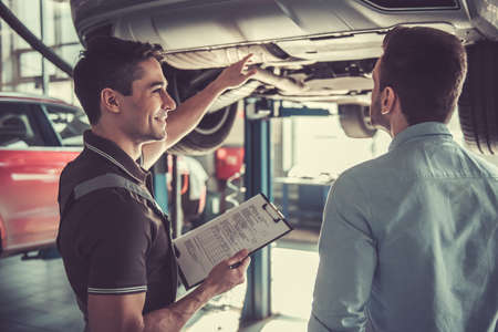 At the auto service. Handsome young auto mechanic in uniform is talking with a client and smiling