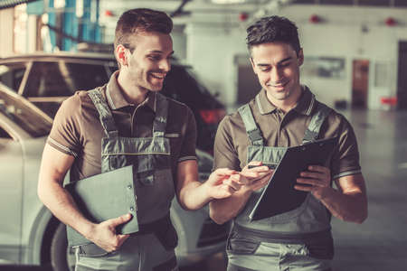 Handsome young auto mechanics in uniform are making notes and smiling while working in auto service