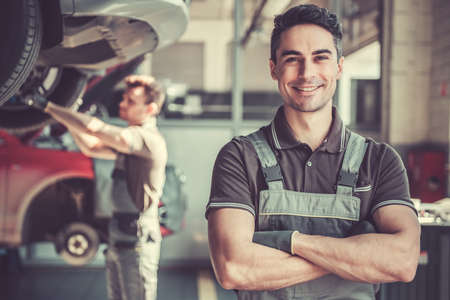 At the auto service. Handsome young auto mechanic in uniform is looking at camera and smiling while his colleague is examining car