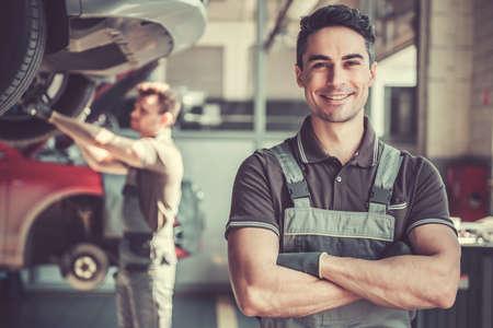 Au service automobile. Beau jeune mécanicien automobile en uniforme regarde la caméra et souriant pendant que son collègue examine la voiture Banque d'images - 76956011