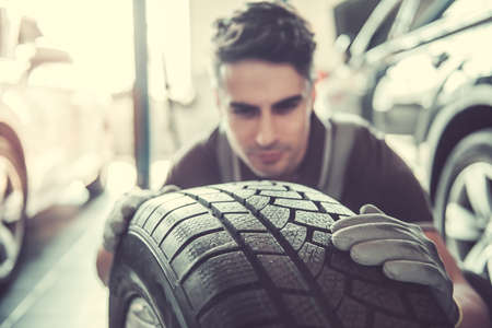 Handsome young auto mechanic in uniform is examining a tire while working in auto service Stock Photo - 76956044